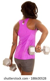 a woman working out with weights in her pink tank, and gray shorts.