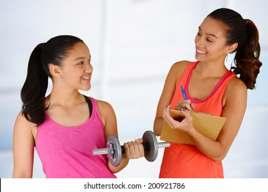 Woman working out while at the gym with a personal trainer