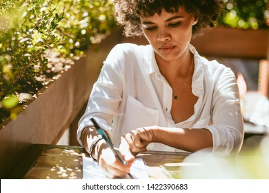 Woman working from a outdoor coffee shop. African female writing notes in a book sitting at a coffeeshop table.