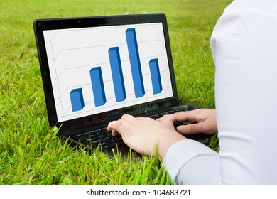 Woman working outdoors on laptop showing graph