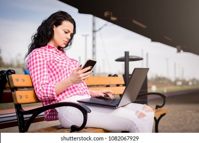 A woman is working outside. A young and attractive girl is working on a laptop. Homeoffice. The woman uses a notebook and a telephone. Checking email messages, news.