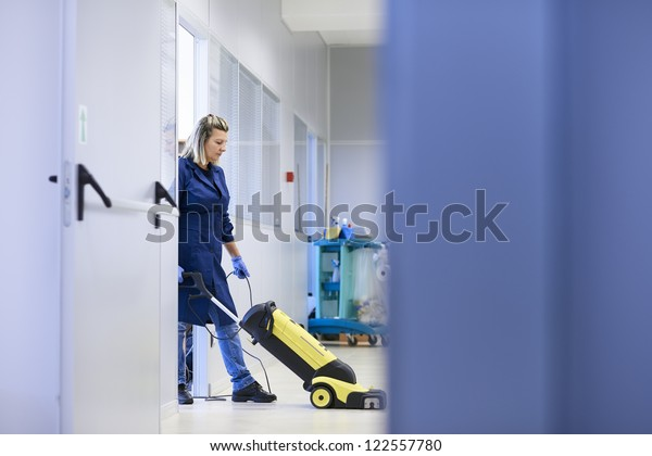 Woman working, professional maid cleaning and washing floor with machinery in industrial building. Full length, copy space