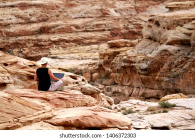 A woman working remotely on her laptop computer high up on a cliff in the Utah desert.
