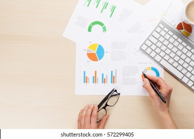 Woman working with reports and charts over wooden office desk. Top view with space for your text