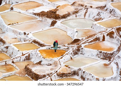 Woman working the salt evaporation ponds in Maras, Peru