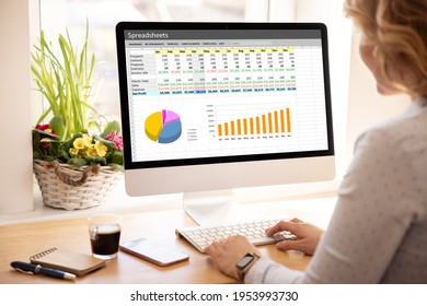 Woman working with spreadsheets on desktop computer