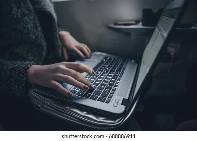 Woman working at train hand on keyboard close up