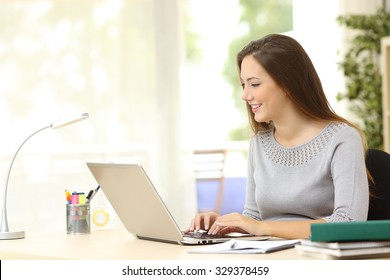 Woman working typing in a laptop on a desk at home