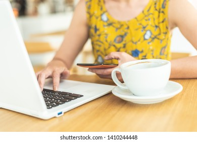 woman working and using cellphone at a coffee shop