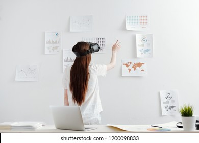 Woman working with virtual reality glasses on analytical reports at the office - Shutterstock ID 1200098833