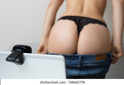 Woman working as webcam model. Takes off her jeans.