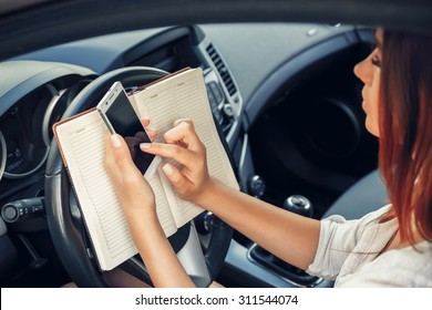 Woman working at the wheel in the car. don't text and drive