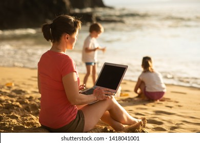 Woman working while kids play, work-life balance concept.
