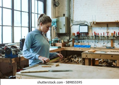 Woman working wood in her atelier