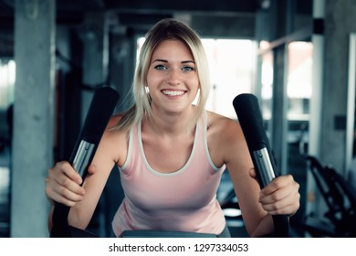 Woman workout cycling exercise in fitness gym., Portrait of pretty attractive caucasian woman cycling training in gym., Beautiful girl in sportswear with smiling while workout.