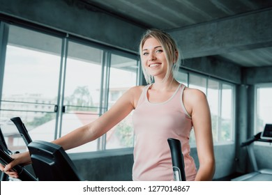 Woman workout elliptical trainer exercise in fitness gym., Portrait of pretty attractive caucasian woman doing elliptical trainer indoor gym., Beautiful girl in sportswear with smiling while workout.