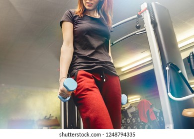woman workout at the gym with dumbbells in hand. active girl with slim body training using fitness equipment at gymnasium. midsection crop with light flare effects