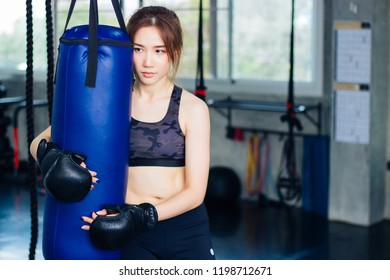 A woman in a workout hugging a sandbag to rest after a heavy boxing practice in a gym.