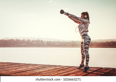Woman workout outdoors with kettlebell performing squat exercise on sunny day