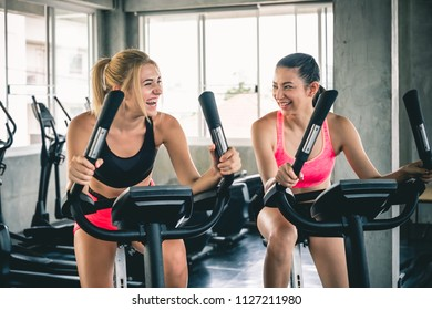 Woman workout at sport gym by cycling machine bike for cardio, gym workout concept