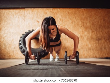 Woman works out her shoulders on the floor in gym