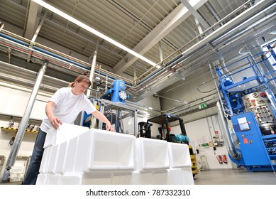 woman works in the shipping department of a company and packs styrofoam components into packages for the customer.