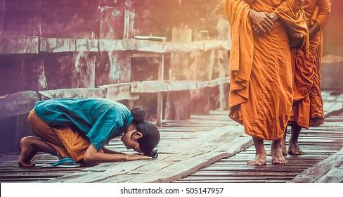 Woman worshiping Buddhist monks  on the wooden bridge.