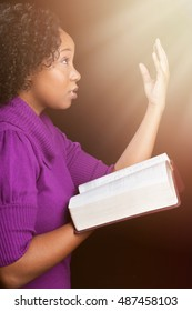 Woman worshiping God holding bible