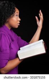 Woman worshipping God holding bible