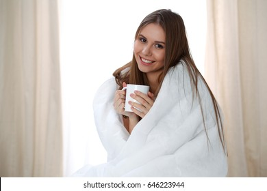 Woman wrapped in a blanket and holds a mug after wake up, entering a day happy and relaxed after good night sleep. Sweet dreams, good morning, new day, weekend, holidays concept
