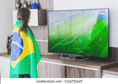 Woman wrapped on the brazilian flag watching a match from the brazilian team in front of the tv.