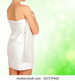 Woman wrapped in a white towel, green blurred background