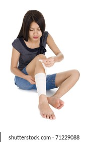 woman wrapping a bandage around her leg, isolated on white background