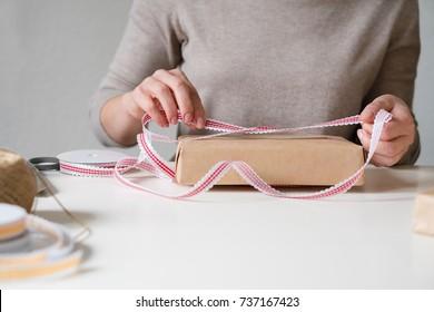 Woman wrapping Christmas gifts. Merry Christmas!