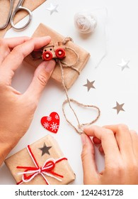 Woman wrapping DIY presents in craft paper. Gifts tied with white and red threads with toy train as decoration.