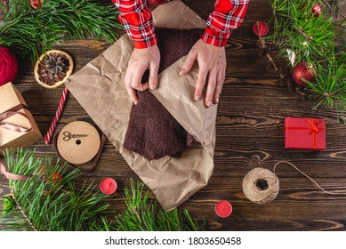 Woman is wrapping the first edge of the needlework wrapping paper that contains the sweater. Step 2 of the Christmas gift packaging process.