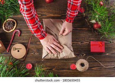 Woman is wrapping the fourth edge of the needlework wrapping paper that contains the sweater. Step 5 of the Christmas gift packaging process.
