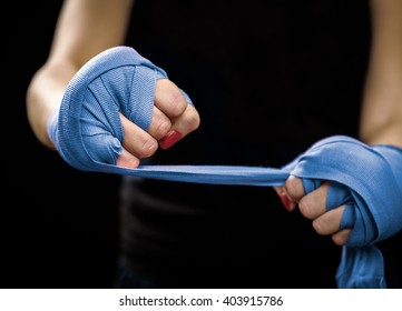Woman is wrapping hands with blue boxing wraps. Self Defense for Women. Isolated on black with red nails. Strong hand and fist, ready for fight and active exercise