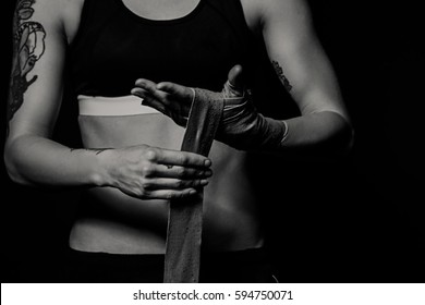 Woman wrapping hands with boxing wraps in dark room. Close-up black and white shot