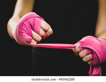 Woman is wrapping hands with pink boxing wraps. Isolated on black with red nails. Strong hand and fist, ready for fight and active exercise. Matte wash image