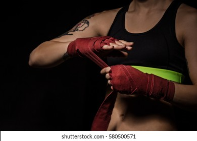 Woman wrapping hands with red boxing wraps in dark room. Close-up shot