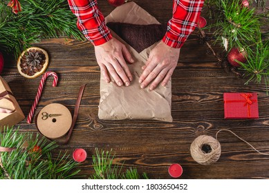 Woman is wrapping the third edge of the needlework wrapping paper that contains the sweater. Step 4 of the Christmas gift packaging process.