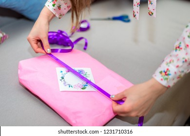 The woman wraps the gift in a pink wrap and decorates with a purple ribbon with a greeting card sitting on the sofa. Gifts, holiday, new year, christmas.