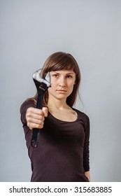 A woman with a wrench. On a gray background.