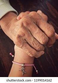 woman wrinkles hands holding smooth hands of teenager. ribbon with breast cancer logo. grandmother and daughter, mom and daughter