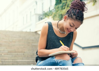 Woman write down the notes at the street, smiling