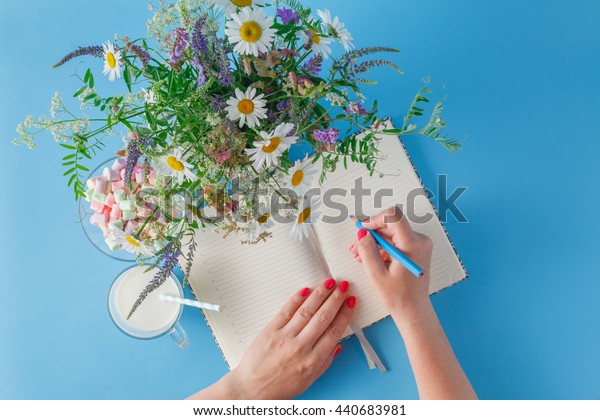Woman write in notebook. Summer bright scene with wildflowers