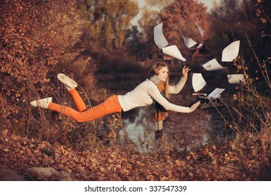 Woman writer levitation in the autumn forest near lake. Concept of freedom and independence in the work