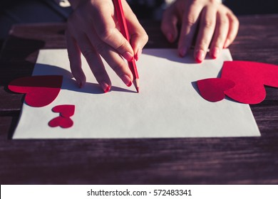 Woman writes love letter on white paper with red heart shape figures.Hand made postcard for Saint Valentines Day celebration.Send letters for your lovers & friends on 14th of February