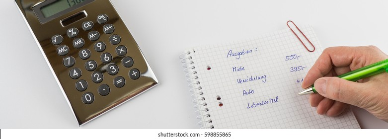 Woman writes me green ballpoint pen on a block the german words for expenses, rent, insurance, car, food, next to a pocket calculator